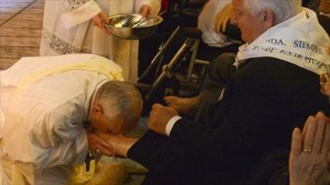 Pope-Francis-L-kisses-the-foot-of-a-man-as-he-performs-the-traditional-Washing-of-the-feet-during-a-visit-at-a-center-for-disabled-people-in-Rome-during-Holy-Week-on-April-17-2014-AFP